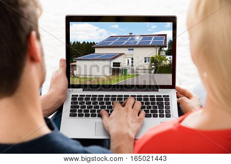 Close-up Of A Young Couple Looking At House On Laptop At Home