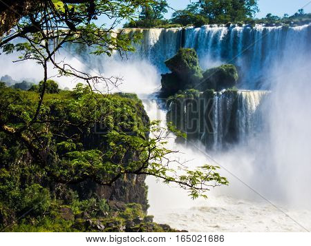 Vew of the water falls in Cataratas del Iguazu park, with a blue sky and a lot of water in the air, misty, rainow.