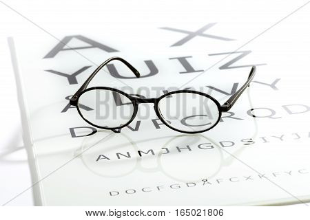 Black oval glasses laying over white glossy eye chart table sight test optometry concept
