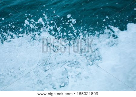 Water splashing. Crystal clear sea water beating against the boat.