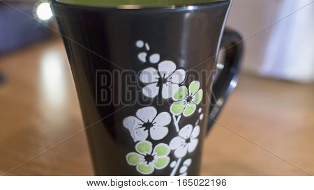 A beautiful black cup with white and green flowers closeup