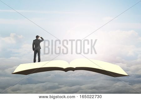 Man Standing And Gazing On Book Flying In Sky