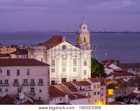 LISBON PORTUGAL - JANUARY 10 2017: Igreja de Santo Estevao in Lisbon Portugal seen from Portas do Sol by night.