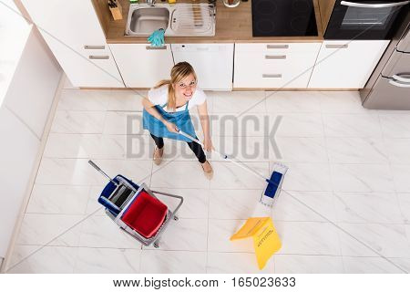 Young Woman Cleaning Floor With Mop In Kitchen At Home