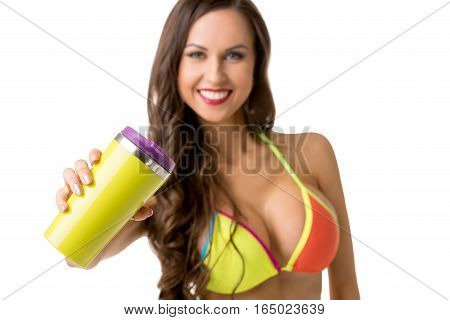 Healhy lifestyle concept. Athletic woman in bright bikini holding shaker with protein cocktail and looking to camera with smile isolated on white background, studio shot