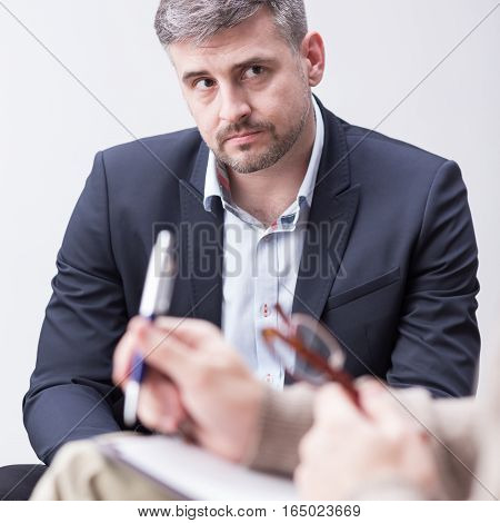 Middle aged handsome man and psychotherapist with notes