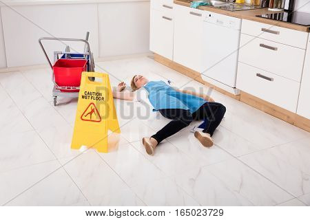 Young Fainted Housemaid Lying On Floor In Kitchen. Accident Compensation Concept