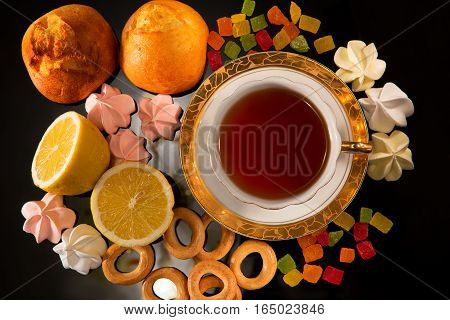 Cup of tea with a lemon and sweets. Still life against a dark background