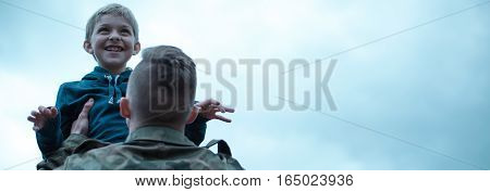 Panoramic view of a soldier returning home holding his son in his arms