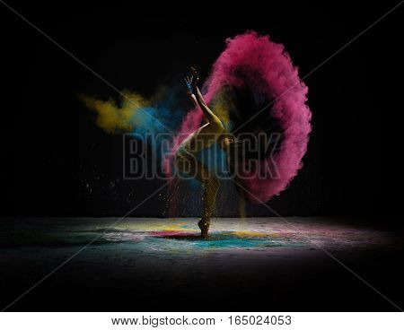 Contemporary art concept - young athletic dancer at dark studio moving in cloud of coloured powder or dry paints