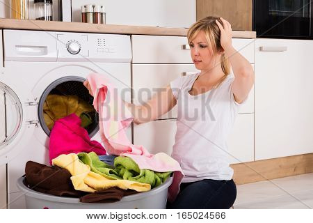 Young Woman Looking At Stains On Cloth After Washing Near Washing Machine At Kitchen