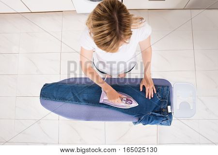 High Angle View Of Young Woman Ironing Jeans On Ironing Board At Home