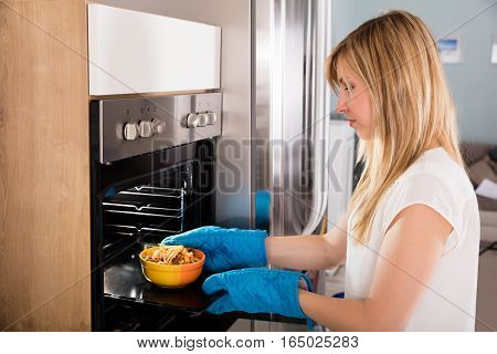 Young Happy Woman Preparing Food In Microwave Oven At Kitchen