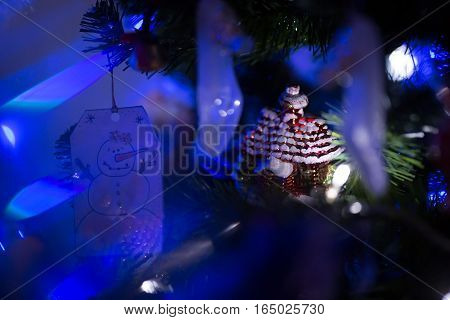 Christmas decoration on fur-tree in blue lights.