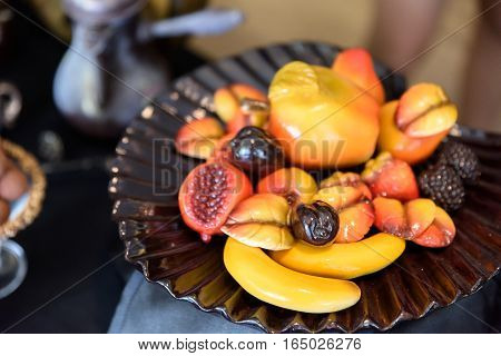 fresh summer fruits and berries on plate, above, rustic background.