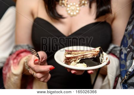 Beautiful girl or a young woman sitting in a restaurant or pastry shop and eating cake. Person cuts the cake and takes a piece with a spoon from plate.