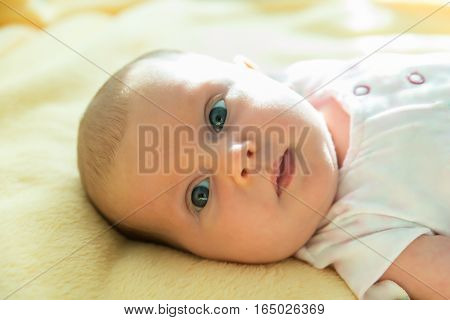 Portrait Of An Adorable Innocent Child Relaxing On Yellow Blanket