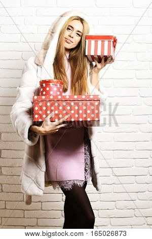 young fashionable sexy pretty woman or girl with long beautiful blonde hair in waist coat of white fur with hood and fashion makeup holding red big presents or gifts on brick wall studio background