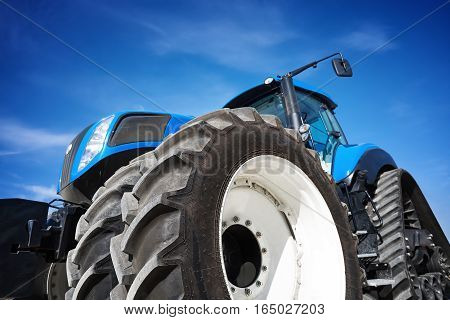 Tractor working on the farm, a modern agricultural transport, a farmer working in the field, tractor on sky background, modern tractor closeup