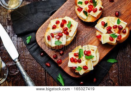 Brie pomegranate balsamic vinegar parsley crostini on wood background