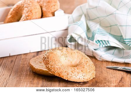 Sesame bagels in wooden crate on wooden table.