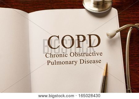 Page with COPD Chronic obstructive pulmonary disease on the table with stethoscope medical concept poster