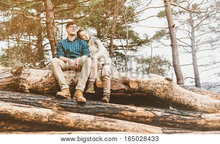 Casual style loving couple resting on stack of felled tree trunks in the forest