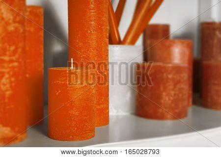 Orange cylindrical candles on white shelf. apartments decor