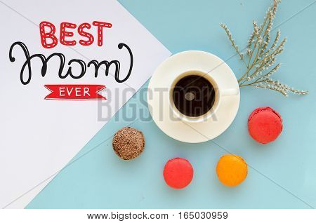 Mother's Day vintage overhead composition of note with love confession, macarons and coffee mug on tender blue background