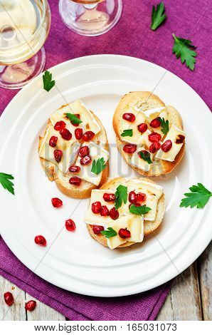 Brie pomegranate balsamic vinegar parsley crostini on wood background