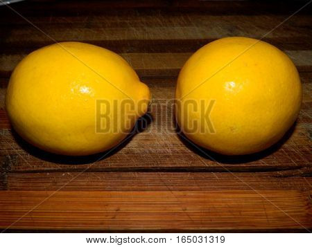 on a wooden chopping board lined with two bright yellow fresh lemon on a horizontal surface in front view