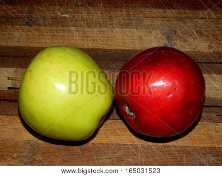 on a wooden chopping board are fresh red and yellow apples and zelenok on a horizontal surface in front view