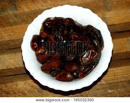 on a wooden chopping board is white plate which are seen to pour a lot of brown dried dates on a horizontal surface