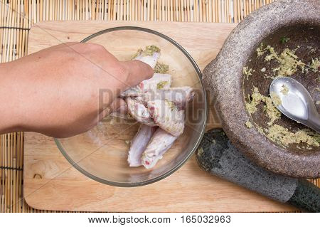 Chef putting seasoning tol chicken wings for cooking / cooking fried chicken wings concept