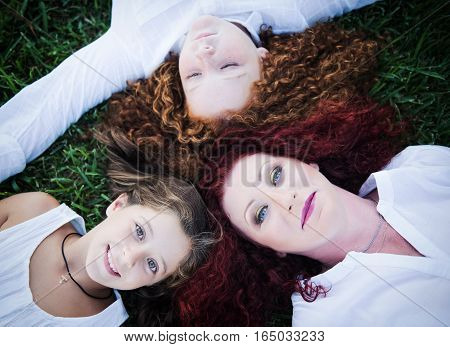 Red-haired mother and her two daughters lie on the grass in the summer