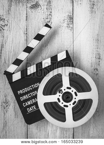 Clapperboards and the reel of film lie on a wooden board.  Black and white photo