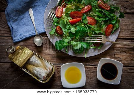 fresh mix of lettuce salad with tomato and a can of sardines in olive oil