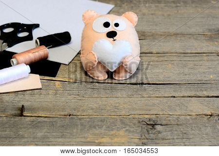 Funny stuffed teddy bear. Teddy bear with a heart made of felt. Handicraft supplies on wooden background with copy space for text. Simple handmade gift on Valentine's day, mother's day