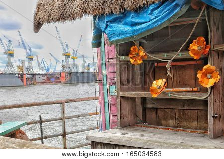 Detail of a city beach in Hamburg. Empty old cupboard decorated by orange flowers and blue curtain. Commercial harbour in the background.Cranes at work.