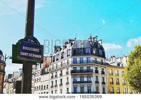 Beatiful view of a corner of Boulevard Saint Germain in Paris. Elegant buildings framed by blue sky and sunny weather.