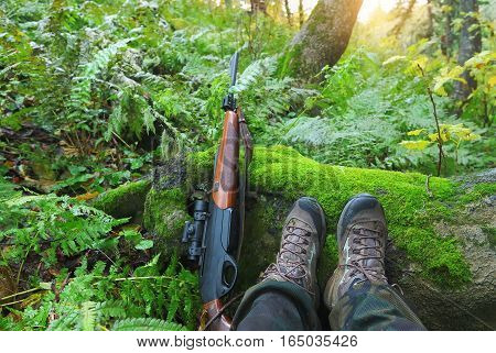 Hunter in the autumn forest with a rifle at sunrise. Legs and the carbine on foreground.