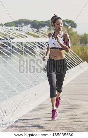 Girl runner listening to music on her armband with touchscreen and headphones