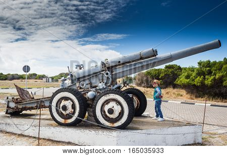 Little boy looking at the Second World War coastal defence howitzer on Robben Island