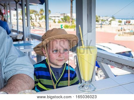 Cute little happy boy anticipating drinking a large banana milkshake