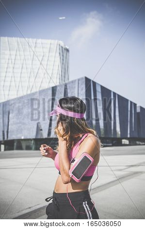 Girl listening to music on her armband with touchscreen and headphones in Barcelona