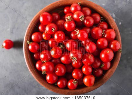 Cherry tomatoes in a clay bowl. Colorful tomatoes Tomatoes background. Fresh tomatoes Healthy food concept. Colorful festive still life. Loosely laid tomatoes in different positions. Copyspace