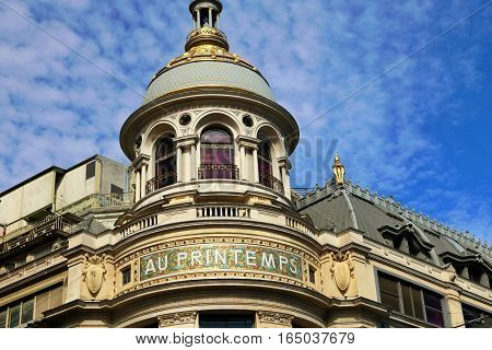 Detail of shopping centre Au Printemps in Paris. Gold dome with blue sky in background. Classical building.