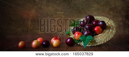 The red and yellow of ripe cherries on the table in a small straw hat. Panorama