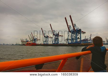 Picture of a kid on a sailing boat in Hamburg harbour. He's admiring the cranes at work.