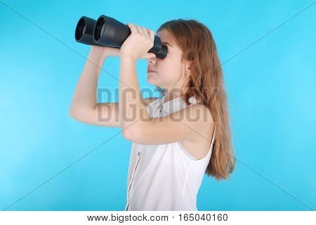 Young girl with binoculars looking up at copy space. Isolated on blue background.
